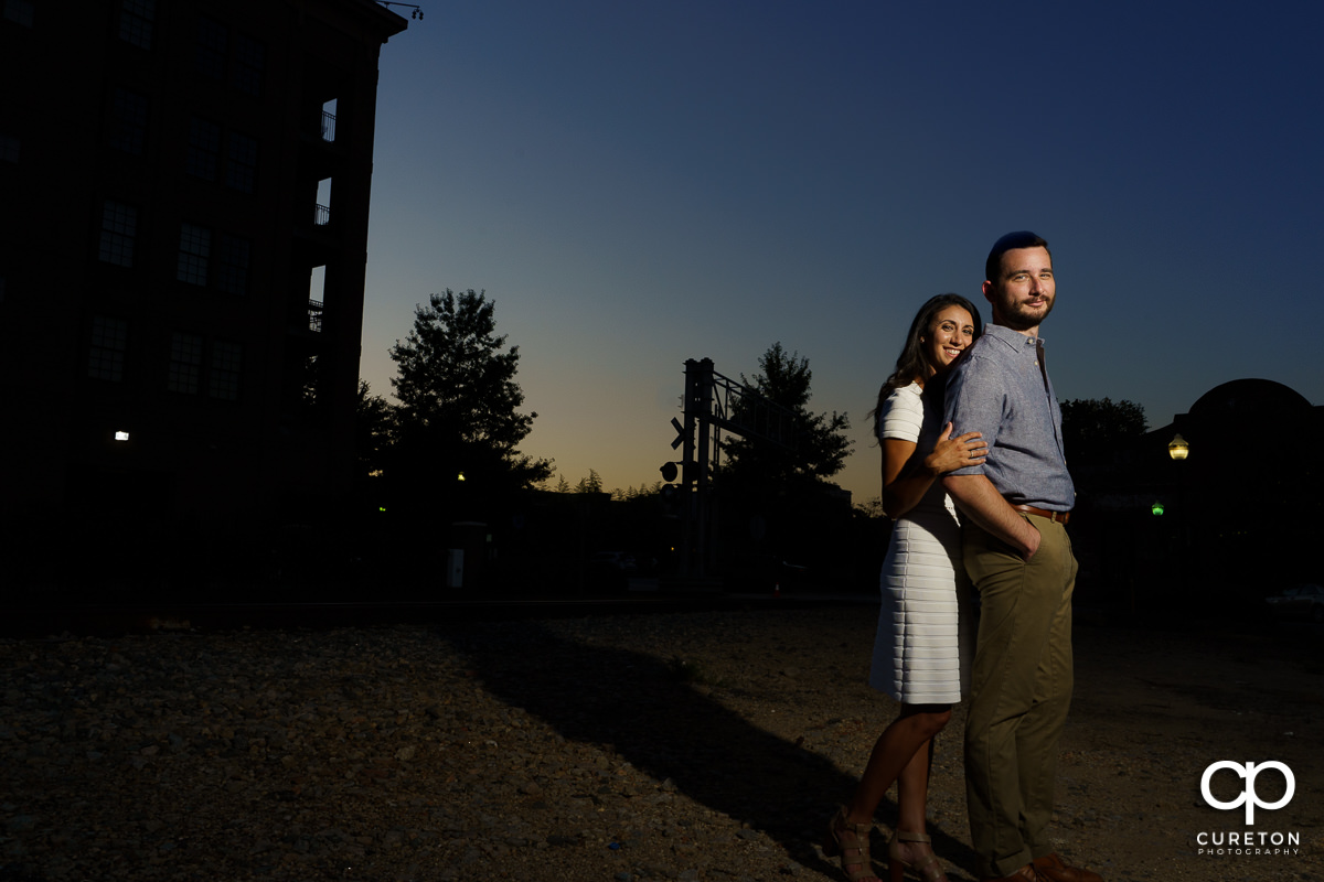 Man and his fiancee in front of some railroad tracks at sunset.