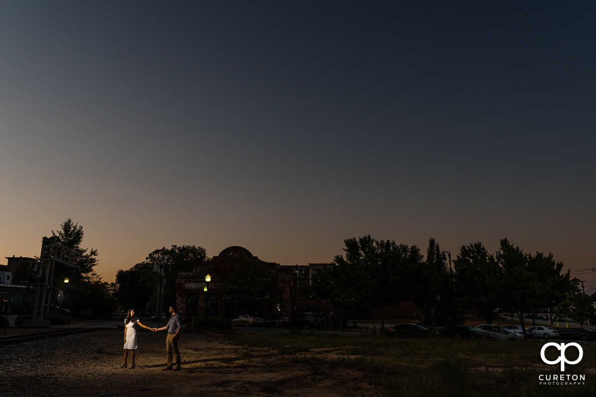Future bride and groom walking hand in hand at sunset in front of The Old Cigar Warehouse during their engagement session.
