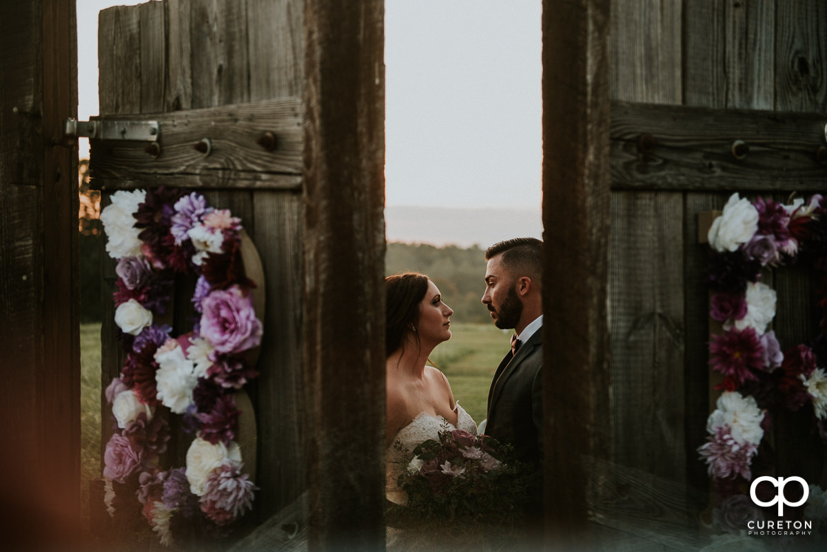 Bride and groom behind the wooden doors in the field before their Lindsey Plantation rustic wedding.