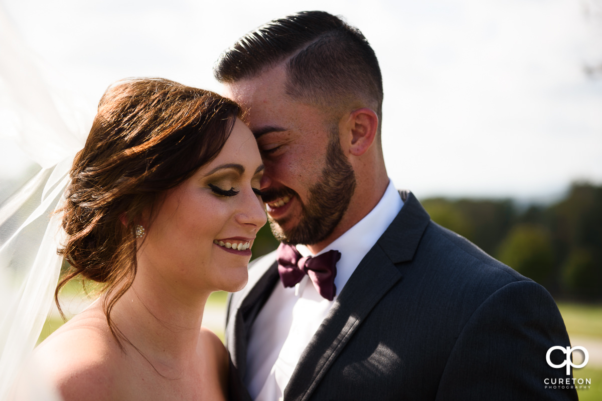Bride and groom smiling before their wedding ceremony.