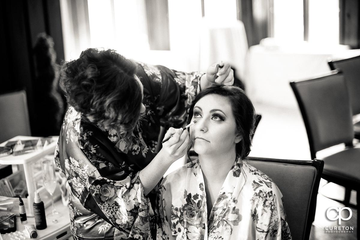 Bride getting her eye makeup applied.