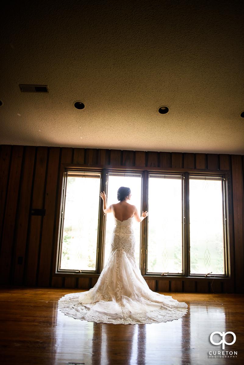 Bride standing in window light from behind.