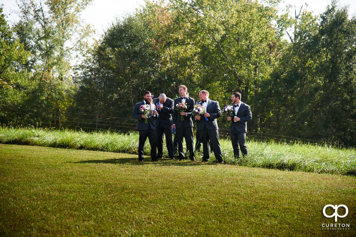 Groomsmen hiding the groom in the field.