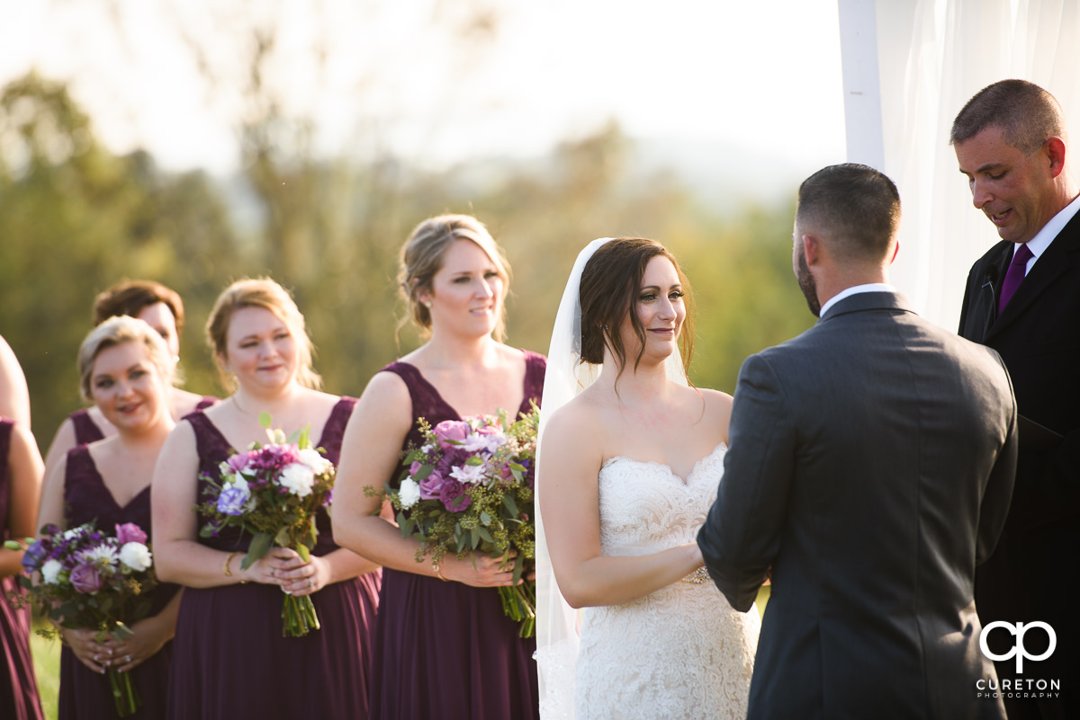 Bride smiling at her groom during the ceremony.
