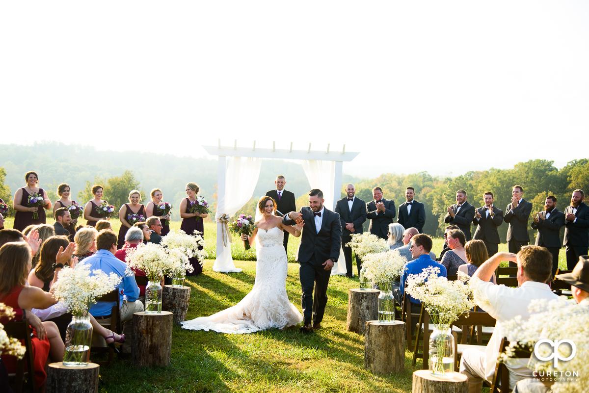 Groom and bride walking back down the aisle at their wedding at Lindsey Plantation.