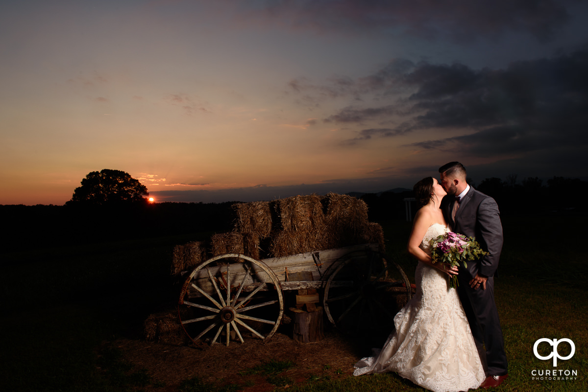 Groom kissing his bride at sunset.
