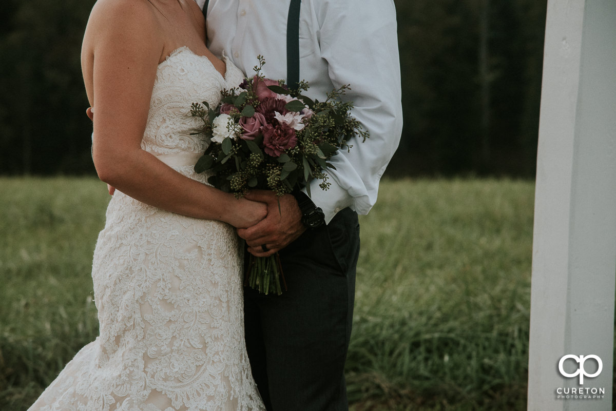 Bride and groom holding hands and a rustic bouquet.