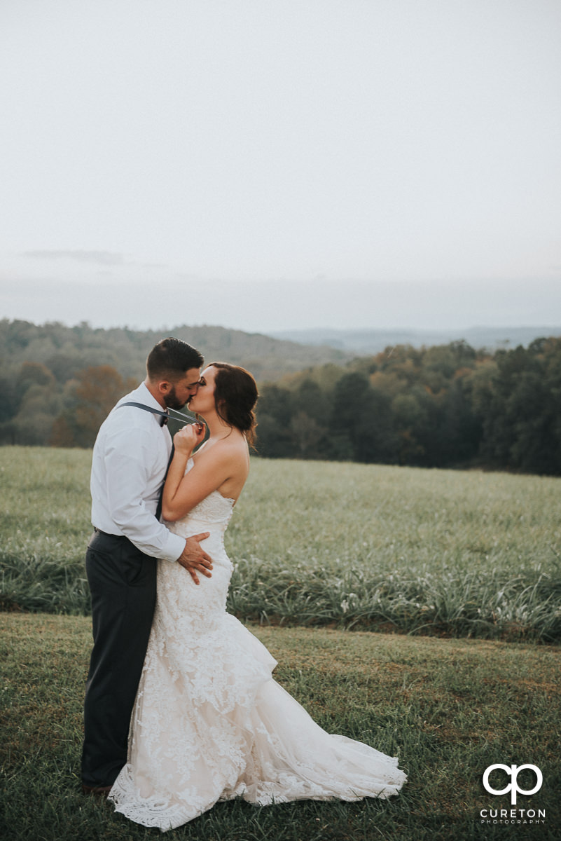 Bride and groom kissing with the mountains in the background.