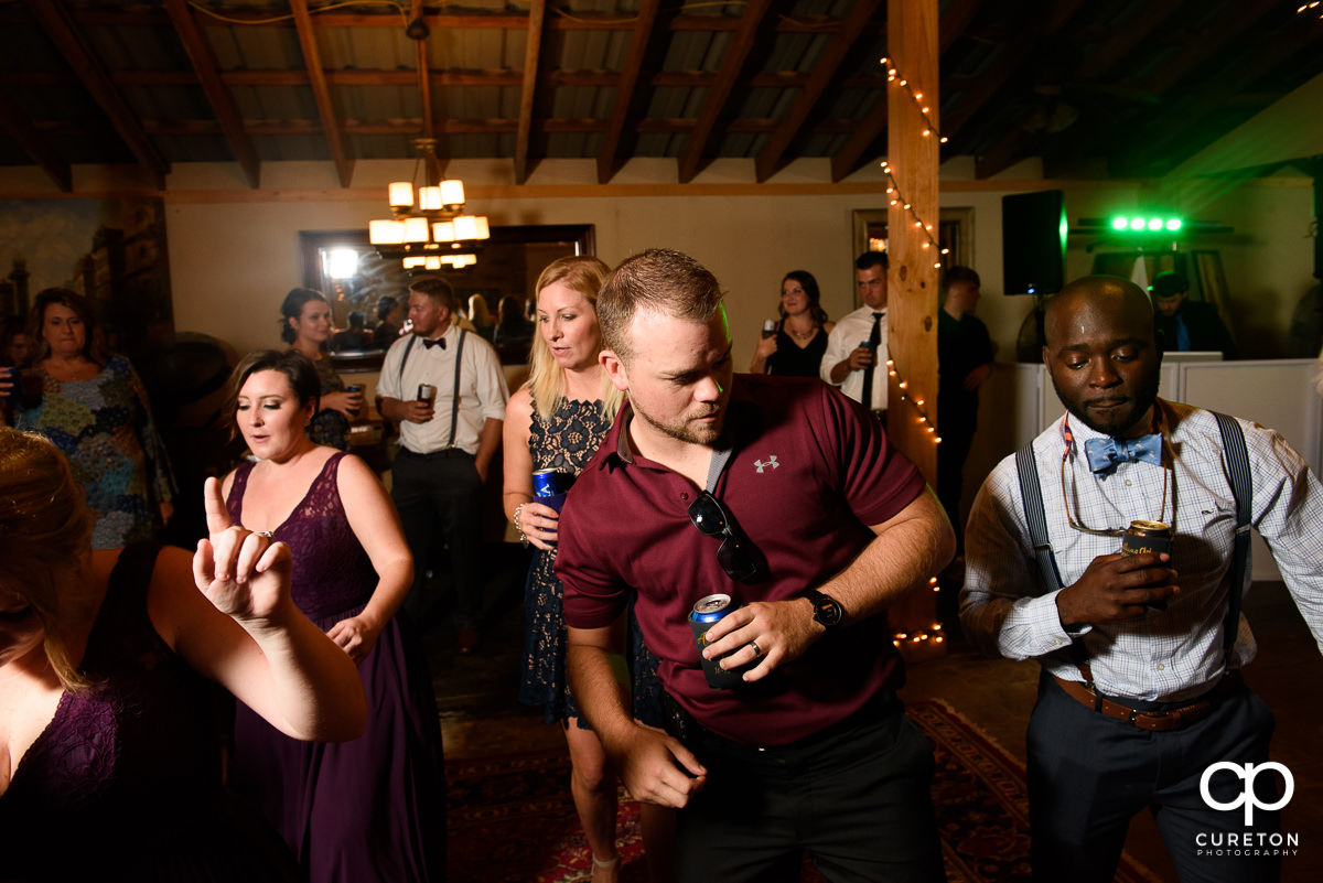 Guests line dancing in the barn at the wedding reception.