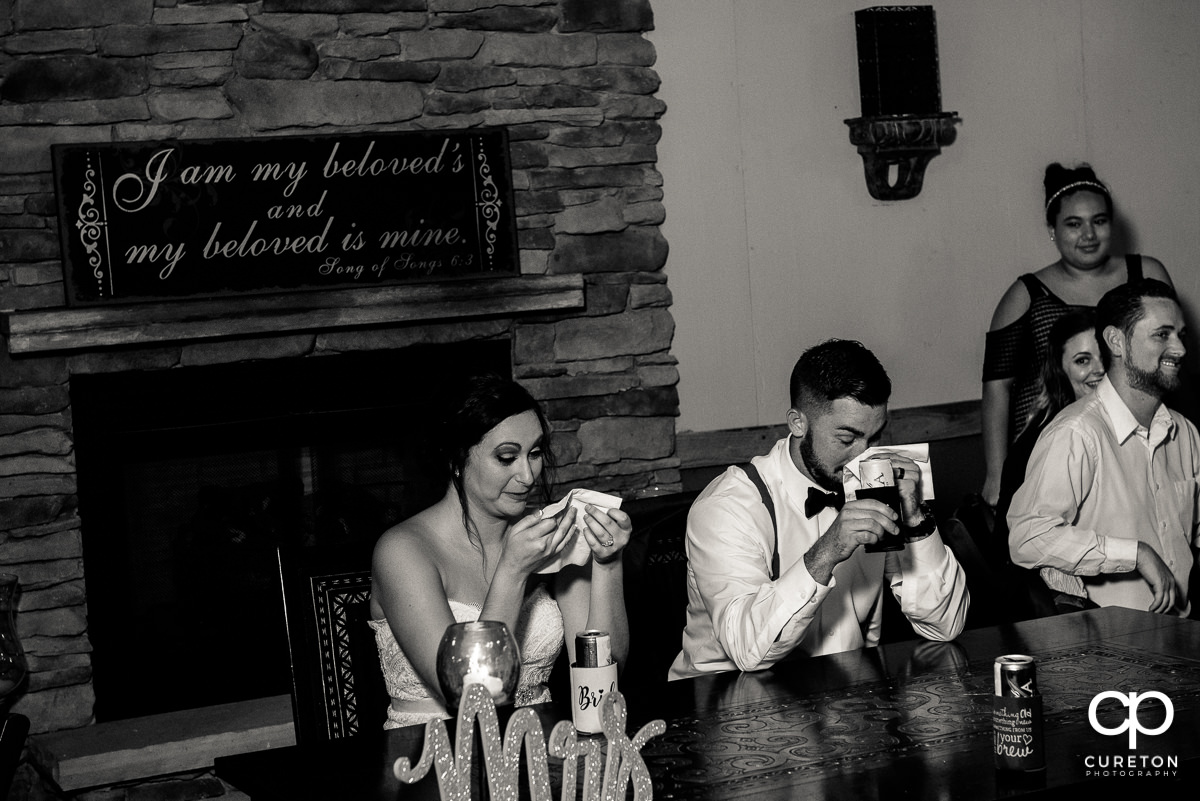 Bride and groom tear up at a speech.
