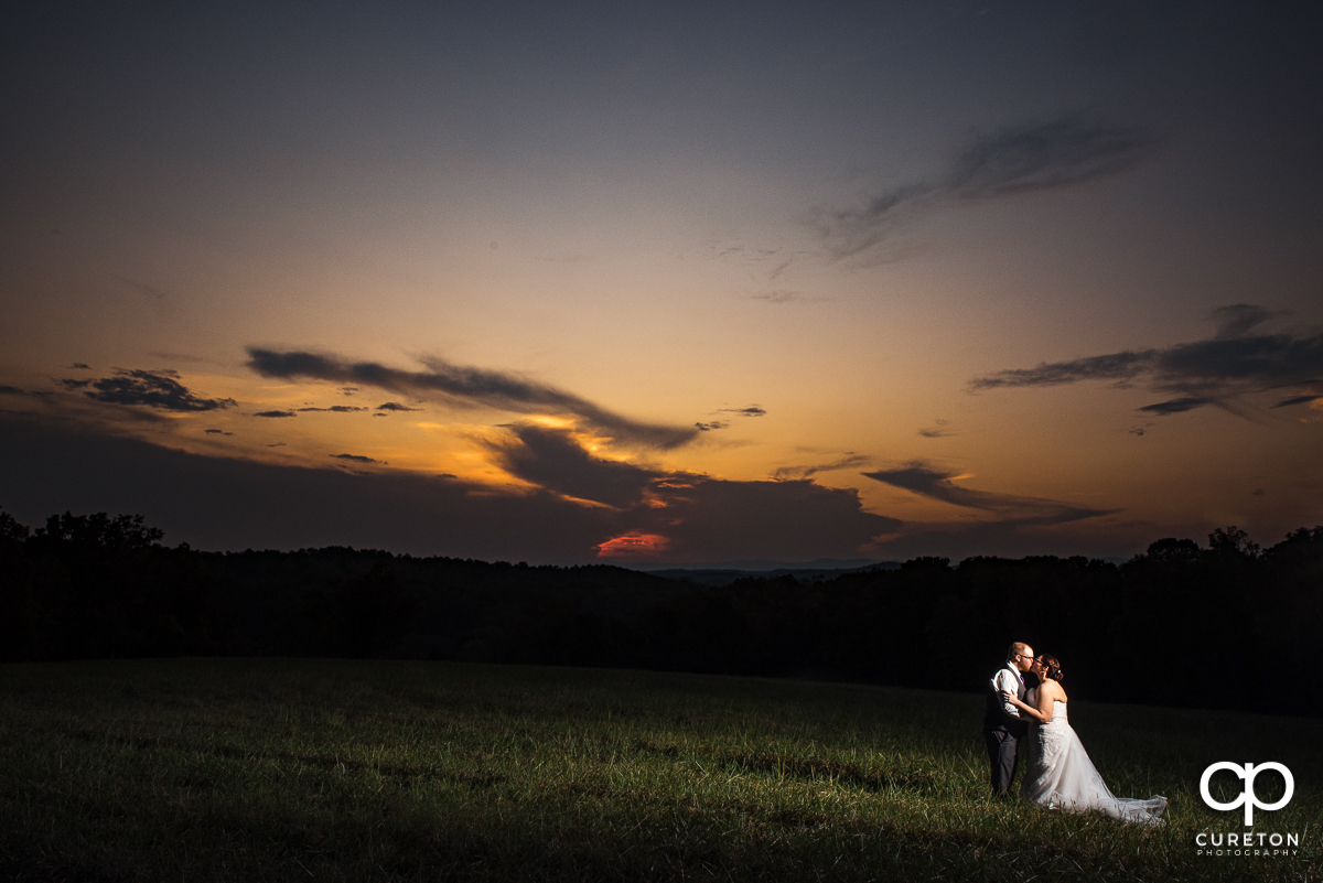 Bride and groom kissing at sunset in a field at their Lindsey Plantation wedding.