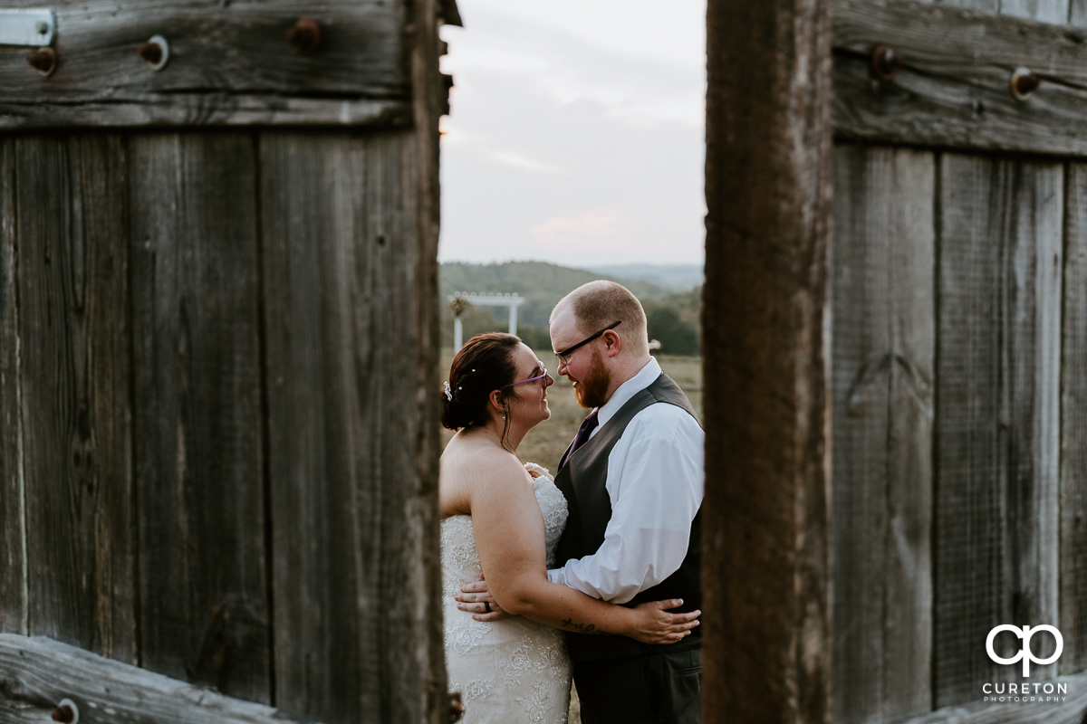 Bride and groom dancing behind some rustic doors at their Lindsey Plantation wedding.