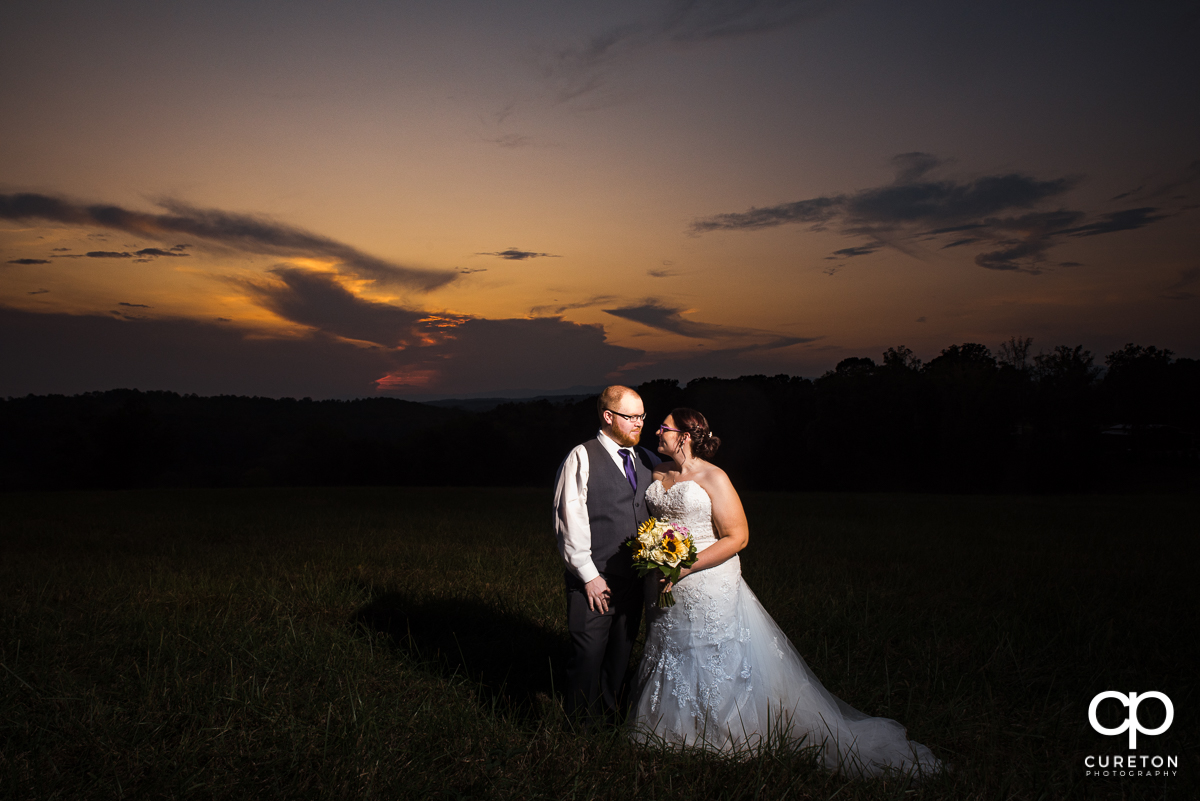 Bride and groom looking at each other in a field at sunset at their Lindsey Plantation wedding.