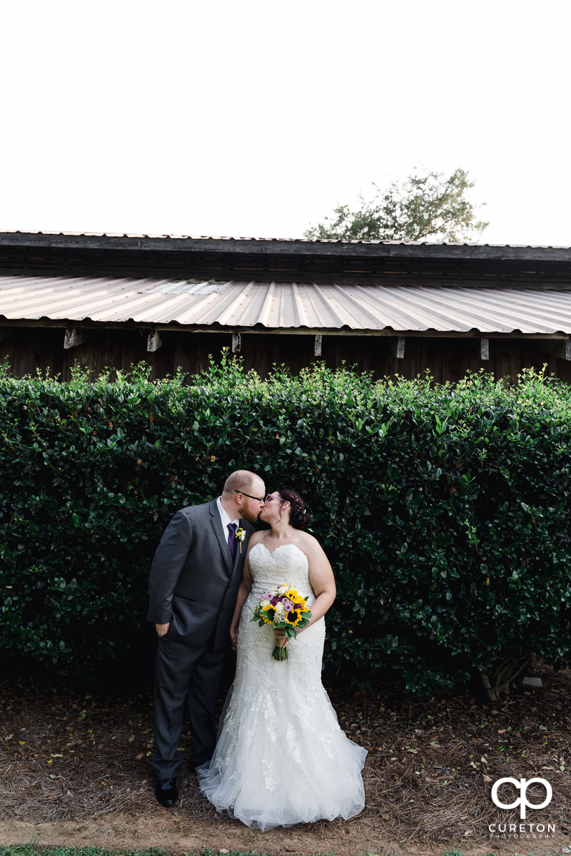 Bride and groom kissing in front of the bushes at their Lindsey Plantation wedding.