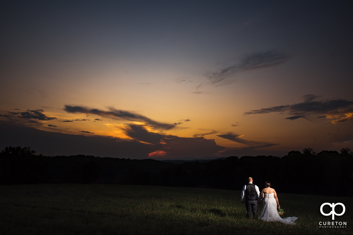 Bride and groom looking out to an amazing sunset at their wedding at Lindsey Plantation in Taylors,SC.