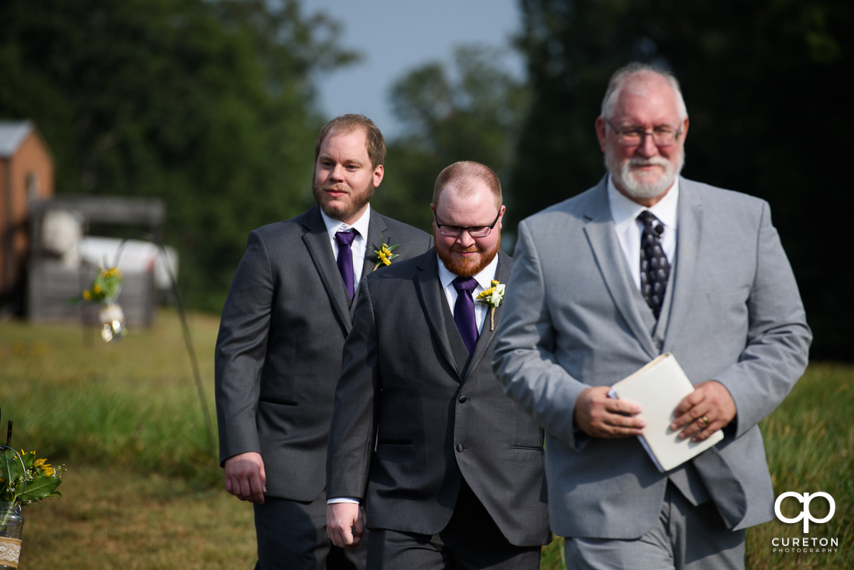 Groom walking down the aisle with the officiant.