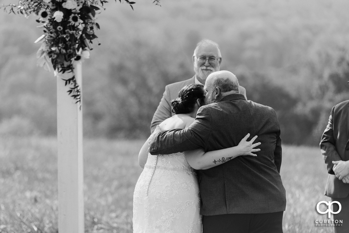 Bride's father hugging his daughter.