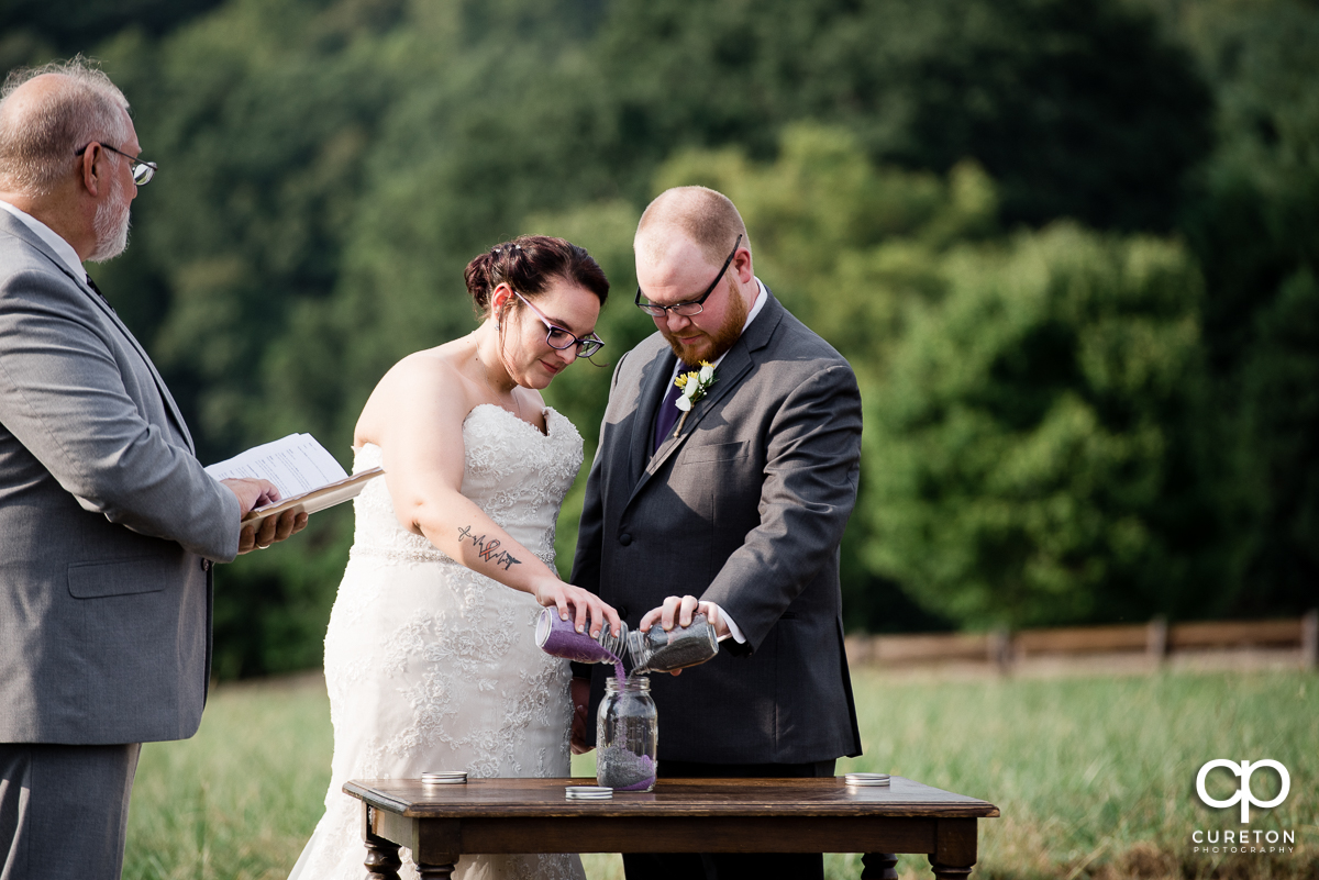 Bride and groom pouring sand into a jar.