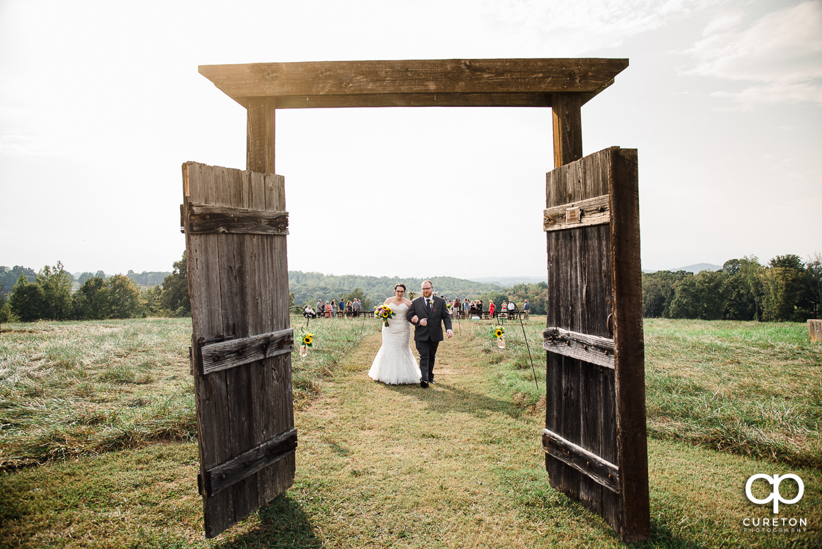 Bride and groom walking back up the aisle towards a pair of rustic doors..
