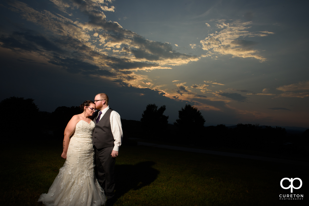 Groom kissing his bride outside Lindsey Plantation at sunset.