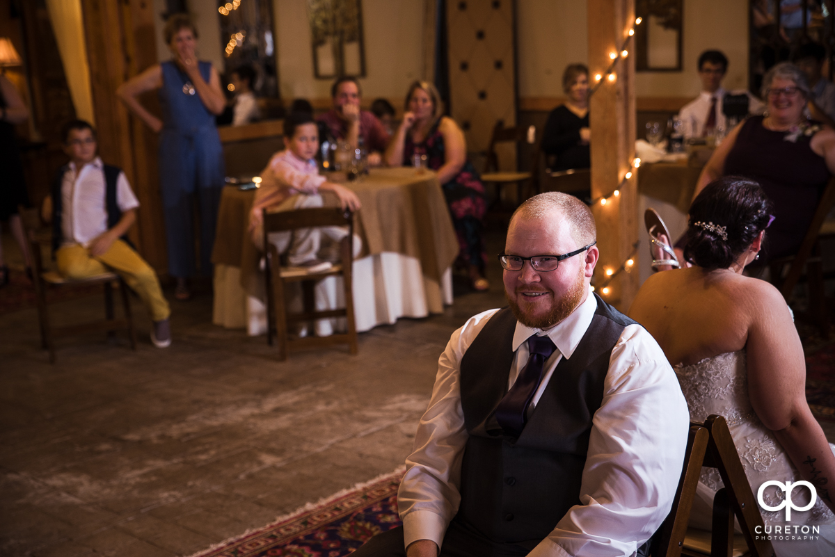 Groom smiling during the shoe game at the reception.
