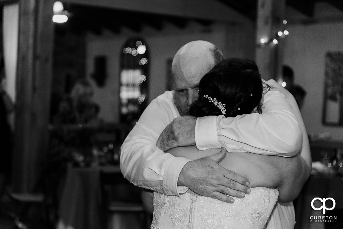 Bride's father hugging her after they shared a dance at the reception.