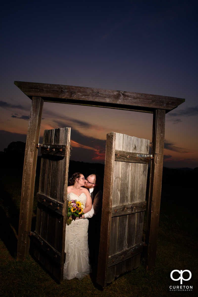 Bride and groom kissing being some rustic doors at sunset.