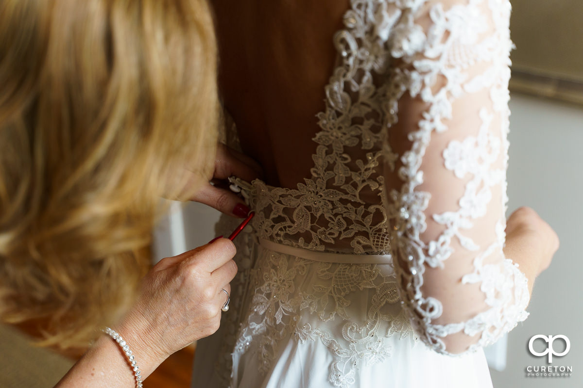 Bride's mom helping her in to her dress before the ceremony.