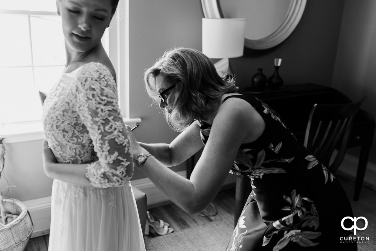 Bride's mother helping her into her dress.