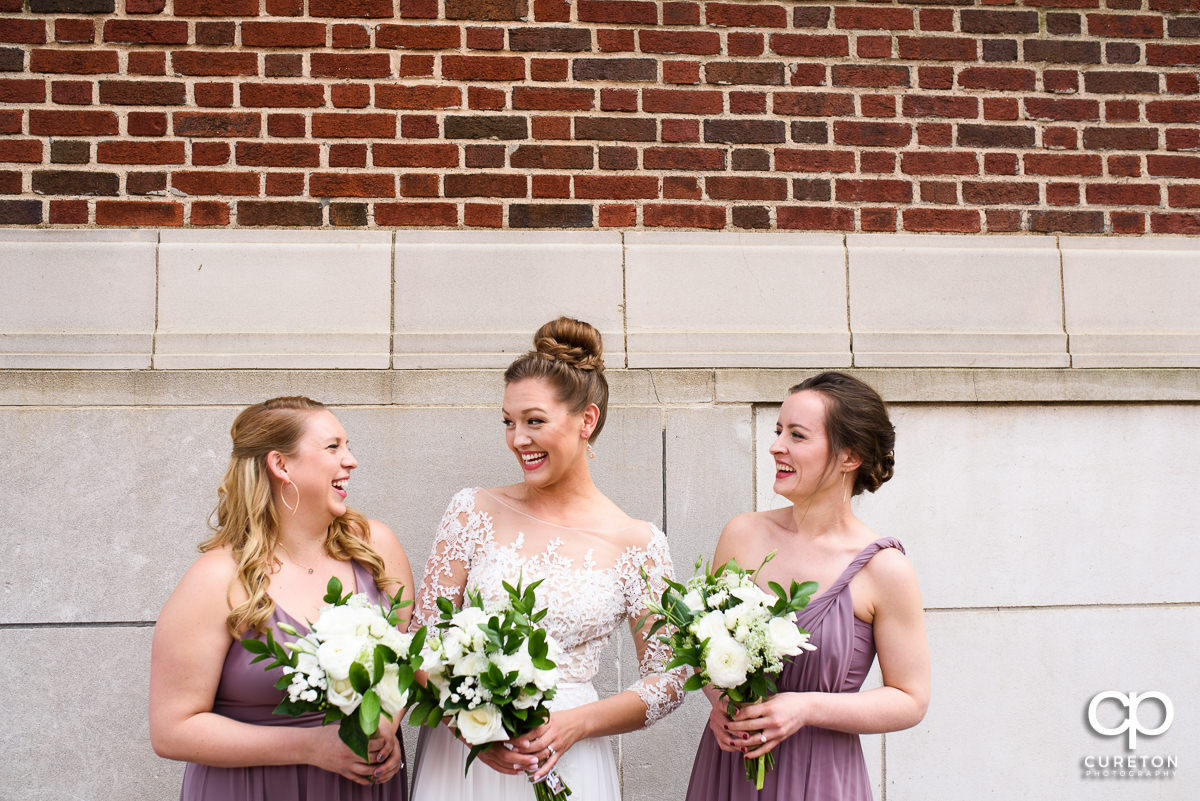 Bride laughing with her bridesmaids.