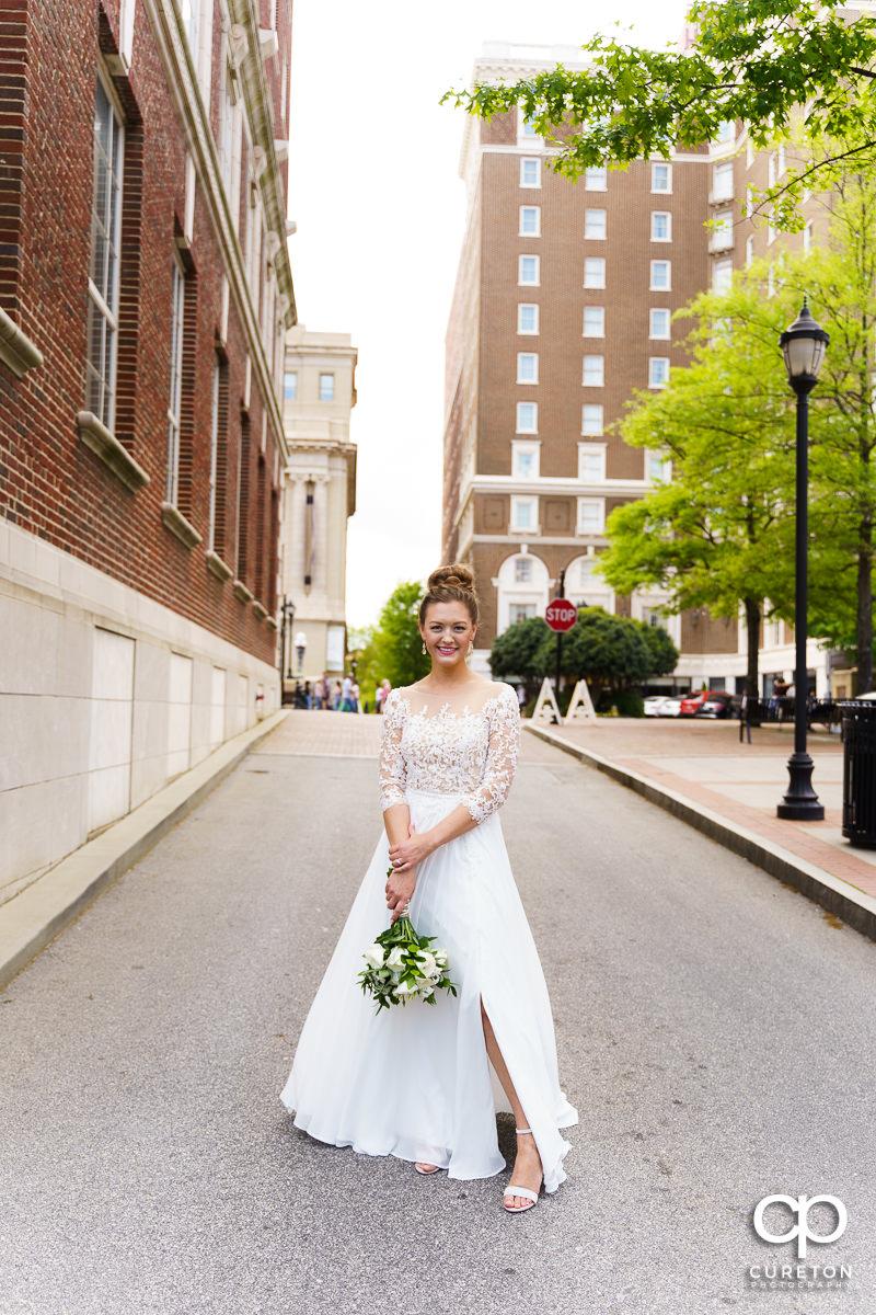 Bride holding her flowers walking down Main Street in downtown Greenville,SC.