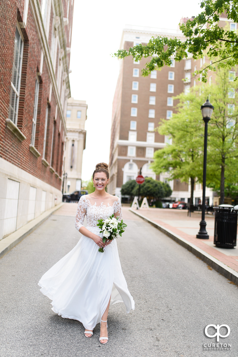Bride smiling as she walks down the street in downtown Greenville to Soby's Loft for her wedding.