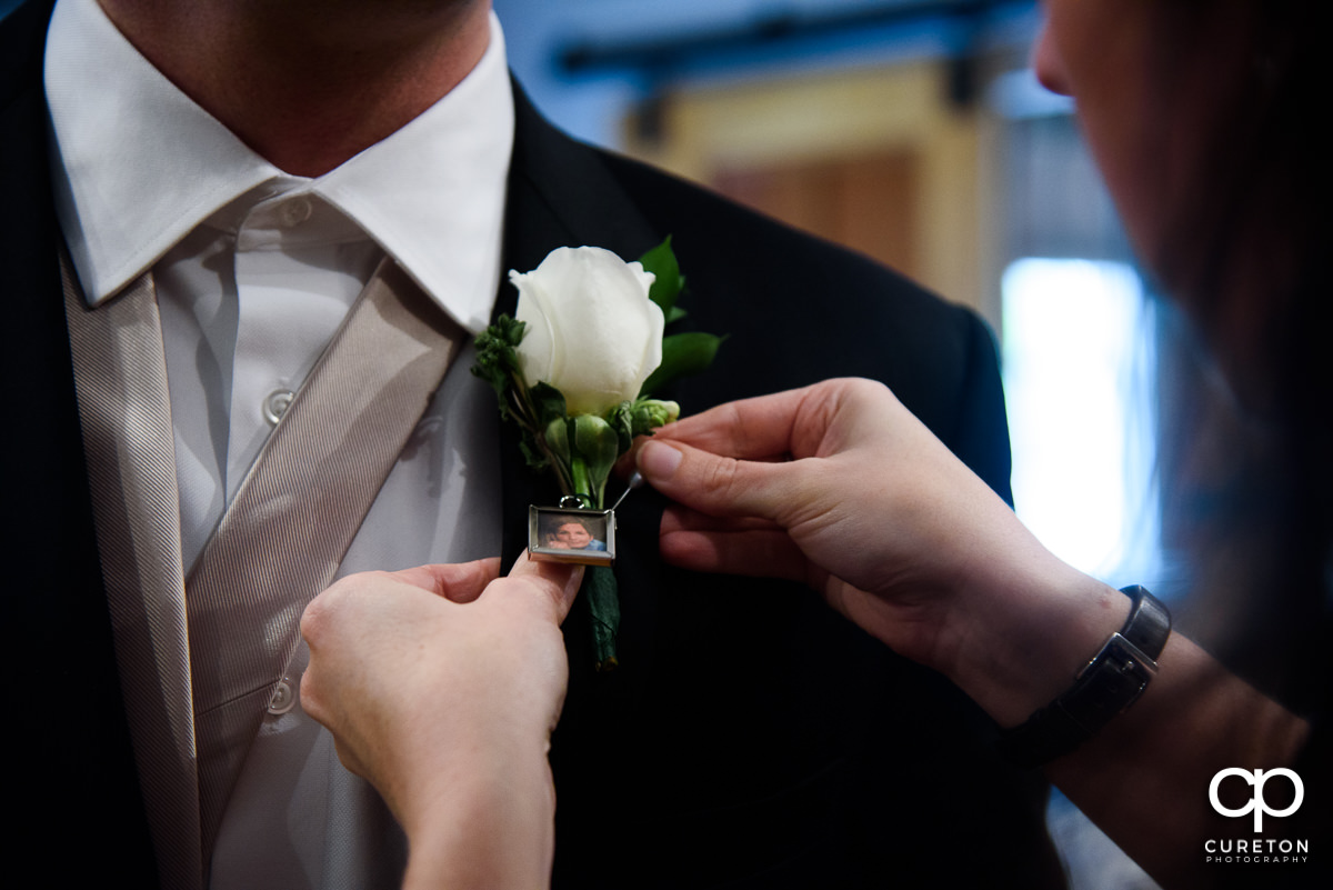 Groom pinning his boutonniere .