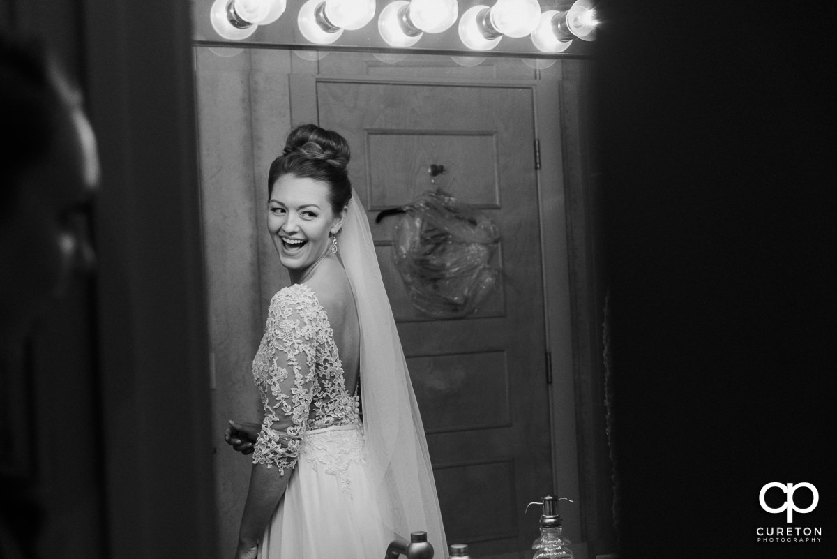 Bride smiling in the mirror as she is getting ready at Soby's Loft in Greenville,SC before the wedding.