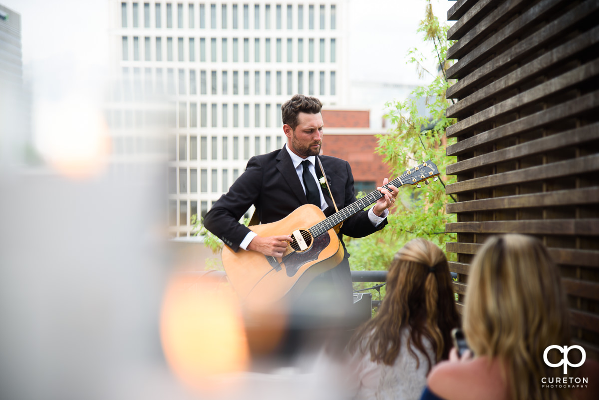 Groomsmen playing guitar at he rooftop ceremony.
