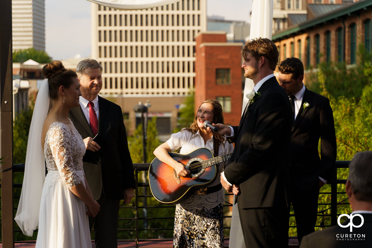 The officiant singing to the couple durin the ceremony.