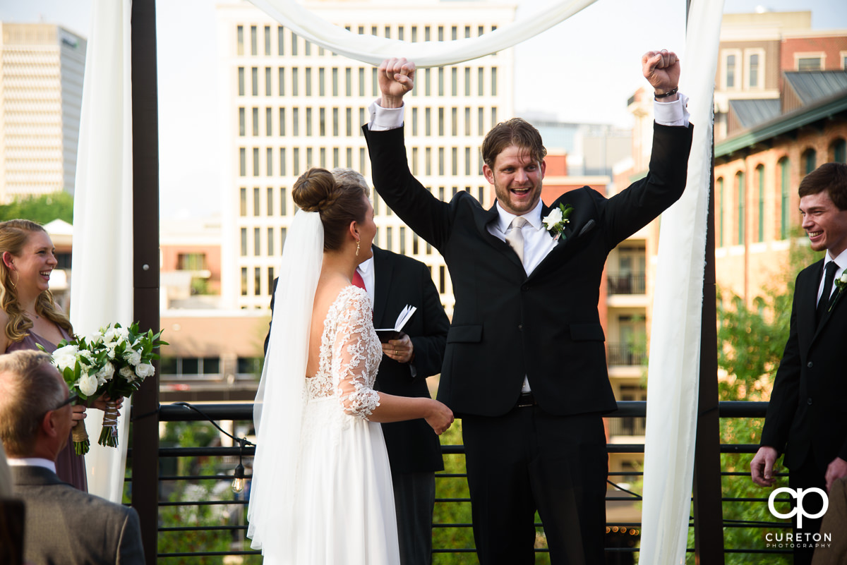 Groom cheering after they are pronounced husband and wife at the rooftop wedding at Soby's Loft in Greenville.