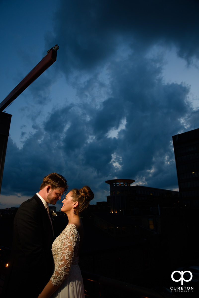 Bride and groom snuggling at sunset on a rooftop during their Loft at Soby's wedding in downtown Greenville,SC.