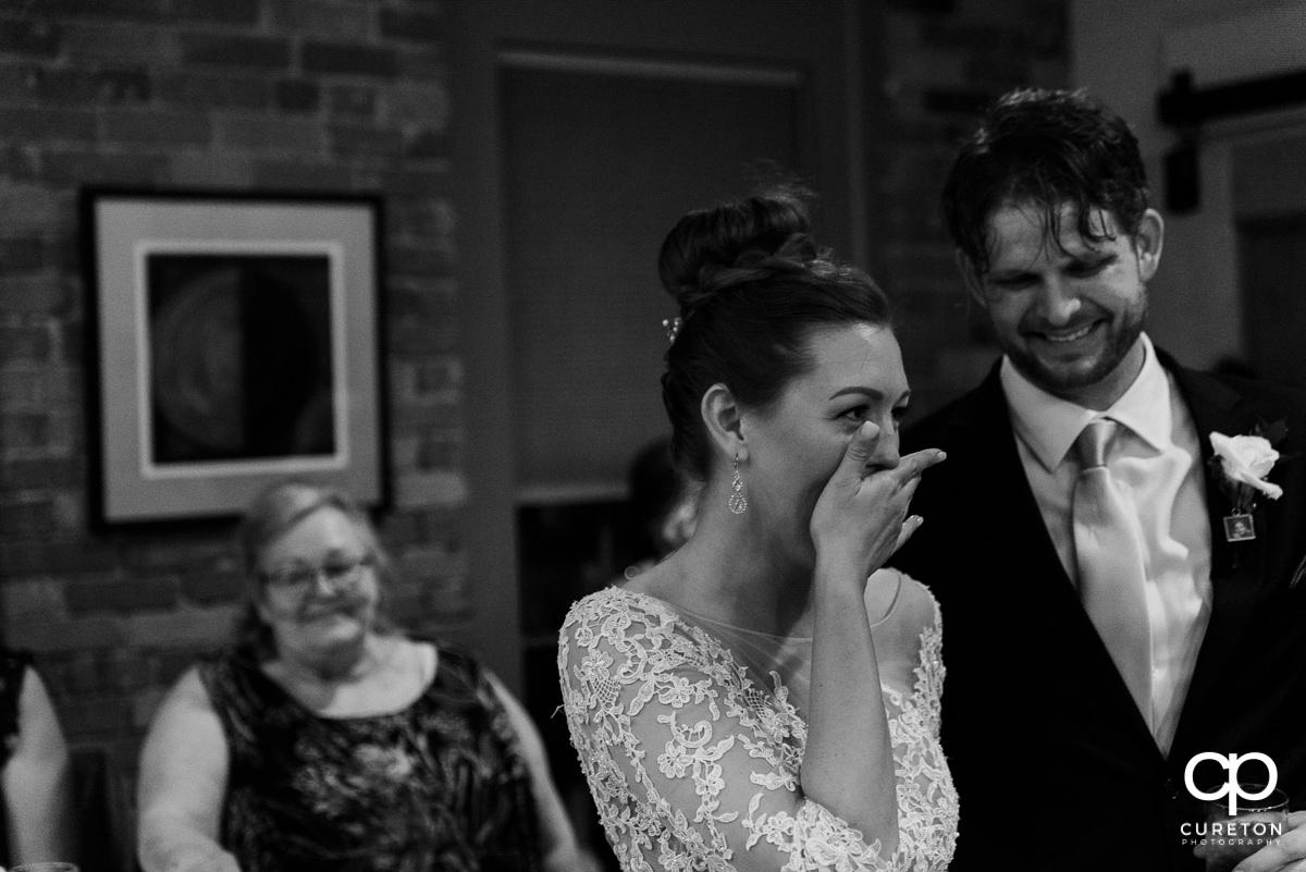 Bride laughing at a wedding speech.