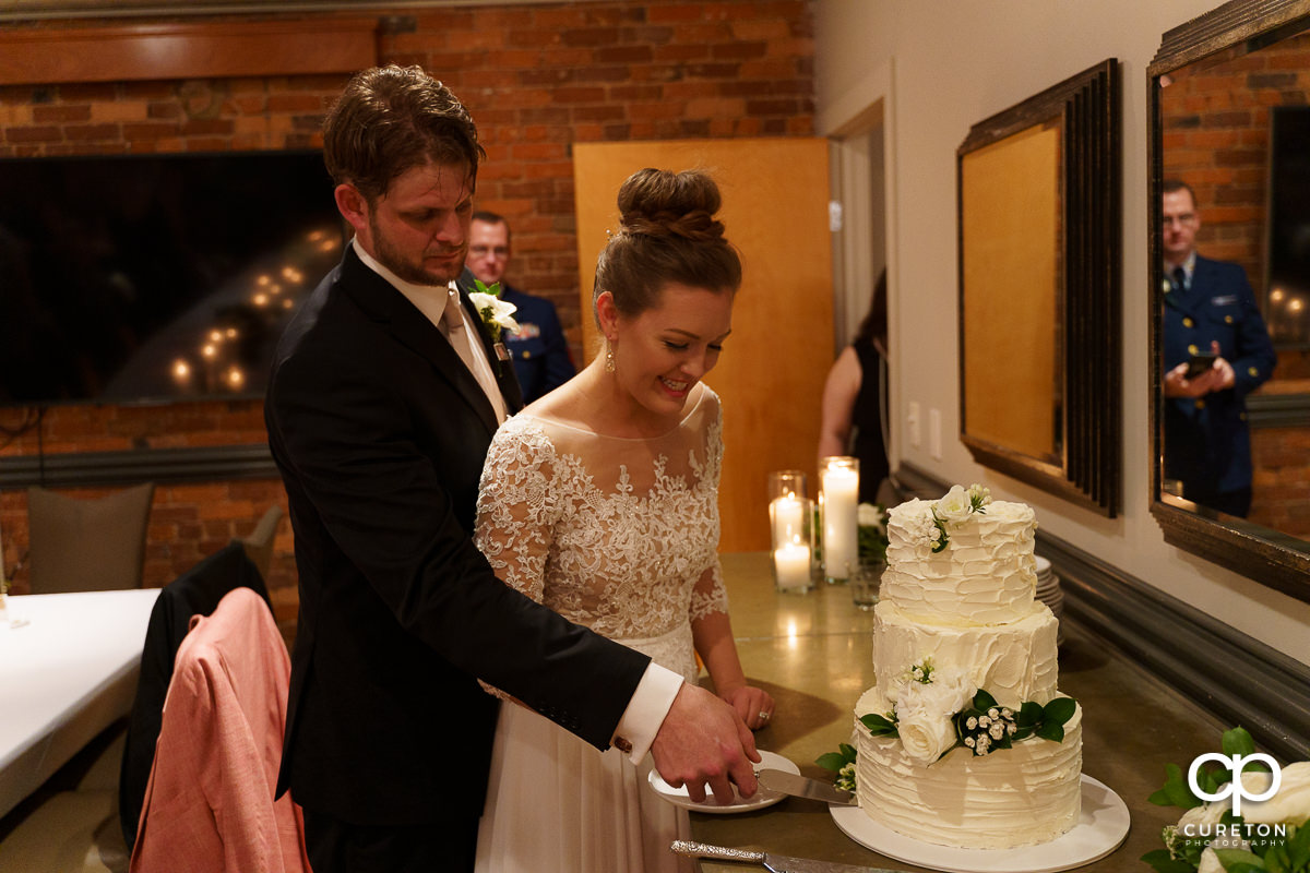 Bride and groom cutting a cake.