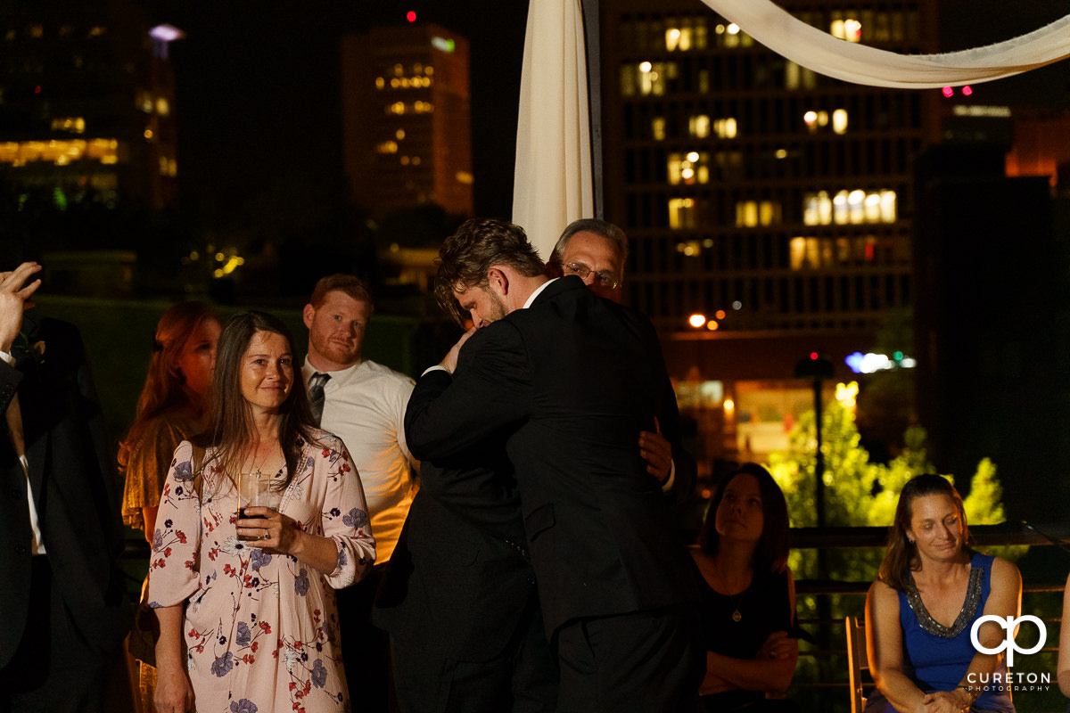 Groom hugging his father at his wedding reception.