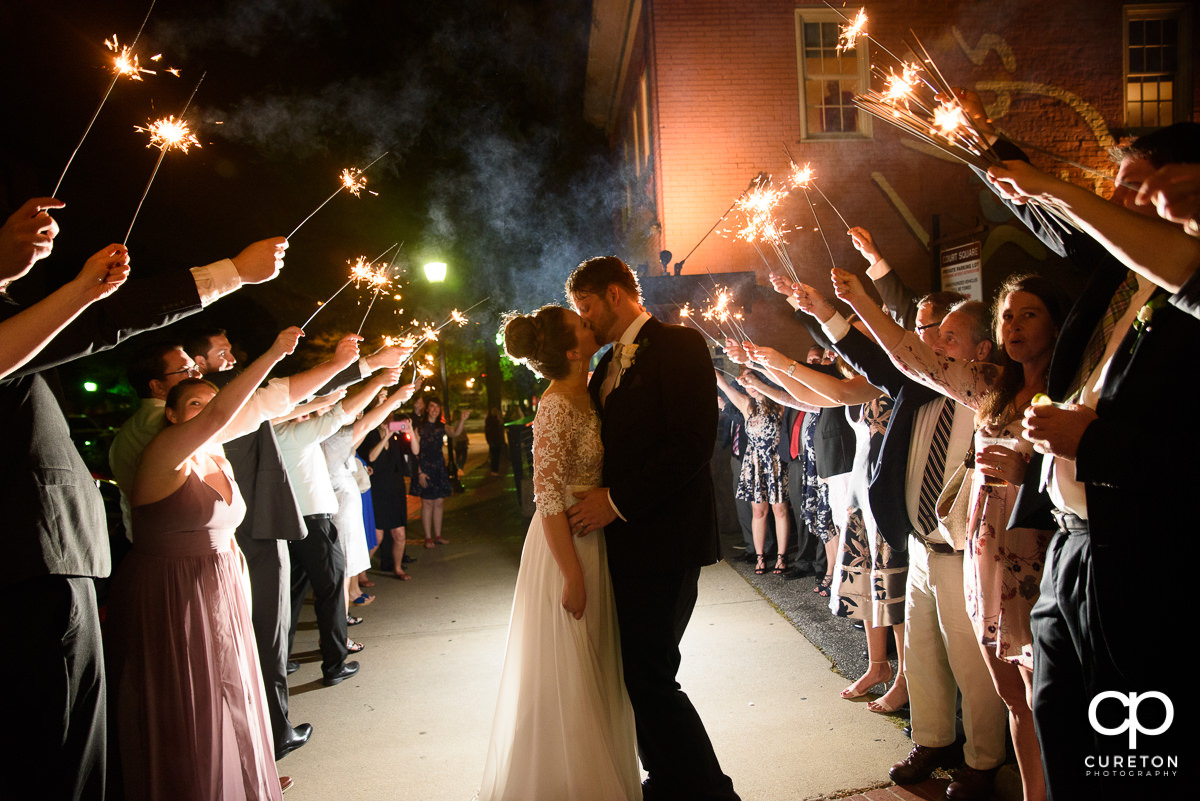 Bride and groom making a grand exit with sparklers at the reception.