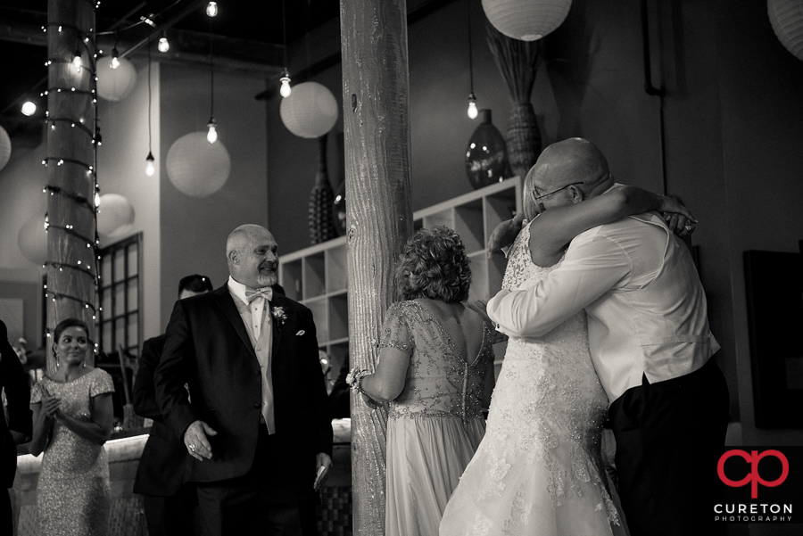 Bride and father hugging.
