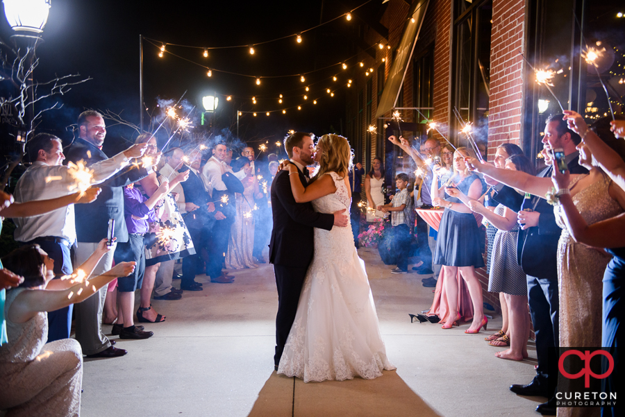 The bride and groom making an epic wedding exit through sparklers at The Loom in Simpsonville.