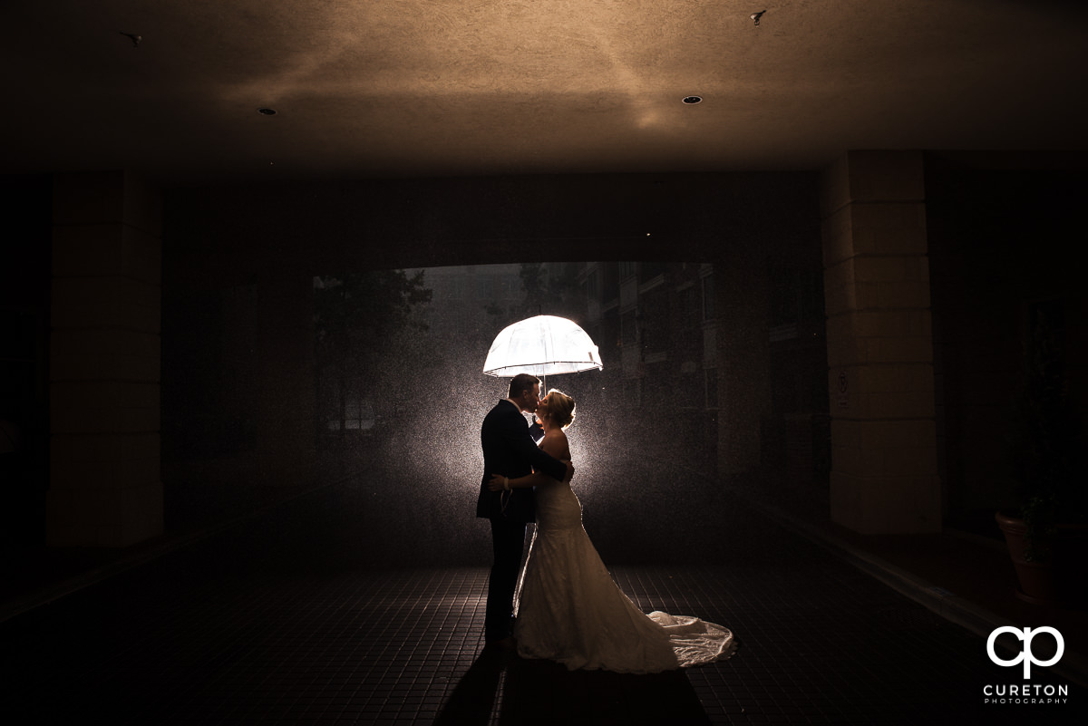Bride and groom kissing underneath an umbrella in the rain before their Mary's at Falls Cottage wedding in downtown Greenville,SC.