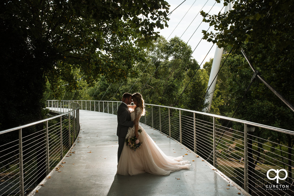 Bride and groom dancing on Liberty Bridge after their Falls Park wedding at Mary's cottage in downtown Greenville,SC.