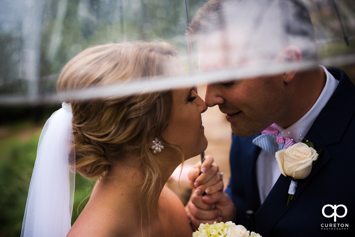 Bride and groom eskimo kissing underneath an umbrella before their Mary's at Falls Cottage wedding in downtown Greenville,SC.