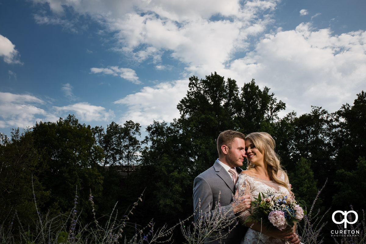 Bride and groom snuggling in some bushes after their Falls Park wedding at Mary's cottage in downtown Greenville,SC.