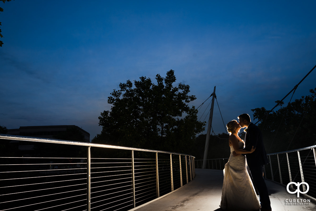 Bride and groom kissing at sunset on the Liberty Bridge after their Mary's at Falls Cottage wedding in downtown Greenville,SC.