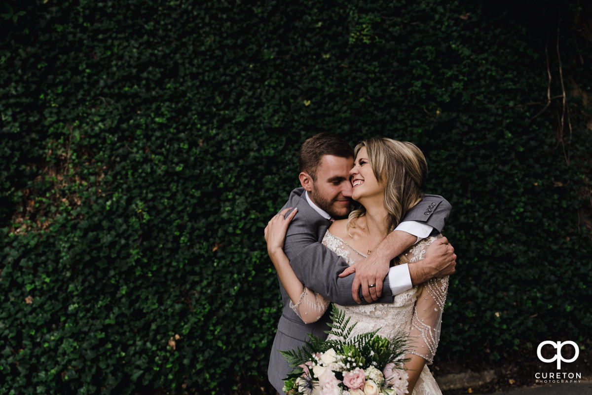 Groom hugging his bride in front of an ivy wall after their Falls Park wedding at Mary's cottage in downtown Greenville,SC.